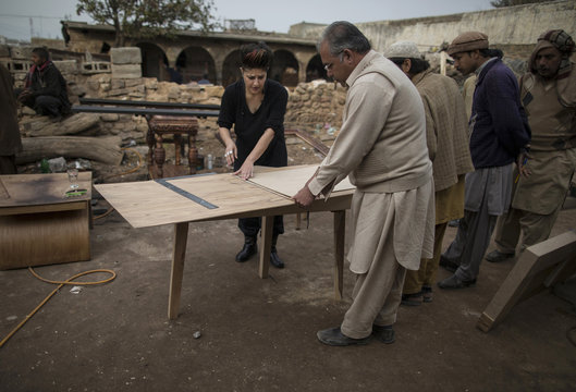Interior designer Zahra Afridi talks to a carpenter at a workshop on the outskirts of Islamabad