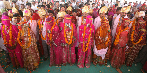 Brides and grooms from the Saraniya community pose for pictures after their wedding ceremony at Vadia village