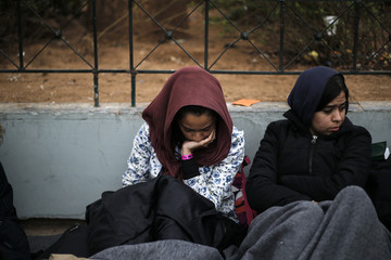 Stranded Afghan migrants rest on Victoria square in Athens