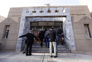 Iraqi policemen search Christians attending a mass on Christmas at St. Joseph Chaldean church in Baghdad