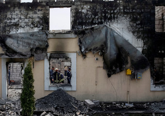 Firefighters work in a burned residential building housing elderly people after a fire broke out, in the village Litochky