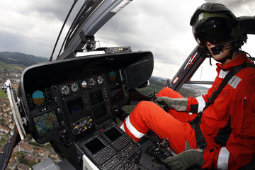 A rescue helicopter pilot from the Swiss air rescue organisation REGA guides his helicopter as it makes its approach flight on the Inselspital hospital during a media presentation in Bern
