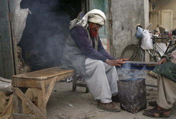 A man with a henna-dyed beard keeps himself warm near a fire outside a shop in Quetta