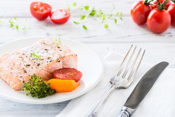 Baked salmon with vegetables on plate. White wooden table