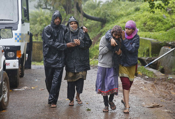 Relatives of the victims who were killed in a landslide weep as they walk in Malin village