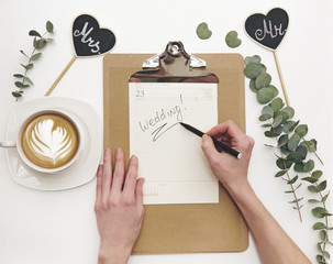 Woman writing word wedding on calendar. Flat lay composition with coffee and decorations. Wedding planner