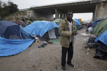 """Sudanese migrant Muhammad poses in front of his tent in the """"New Jungle"""" makeshift camp as unseasonably cool temperatures arrive in Calais"""