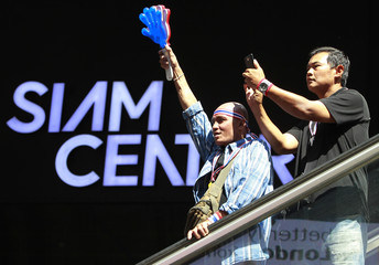 Anti-government protesters use a noise maker as they gather outside the Siam Center shopping mall in central Bangkok