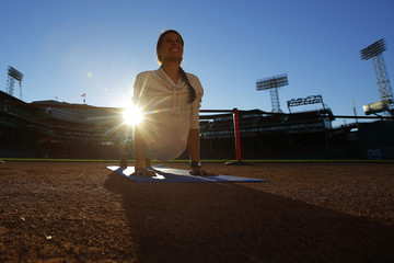Rebecca Pacheco warms up and poses for photographs before leading the first ever public yoga session at Fenway Park, home of MLB's Boston Red Sox, in Boston