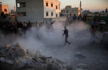 Men search for survivors after an air strike by a fighter jet loyal to Syrian President Bashar al-Assad in Azaz city
