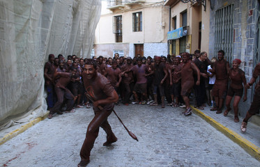 """Revellers covered in paint take part in the annual """"Cascamorras"""" festival in Guadix"""