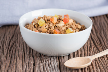 Granola with dried fruits and nuts in white bowl.