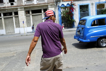 A man wears a hat printed with the U.S. flag in a street in Havana