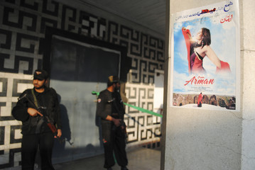 The poster of a Pashto language film is pictured as policemen guard the entrance of a cinema at the site of a grenades attack in Peshawar