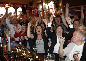 People react as they watch the men's singles final tennis match between Andy Murray of Britain and Roger Federer of Switzerland at the Wimbledon Tennis Championships in London, on a television screen in a pub in Murray's hometown of Dunblane, Scotland