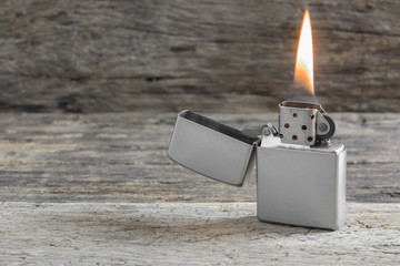 classic silver metal lighter with flame on old and crack wooden surface, close up