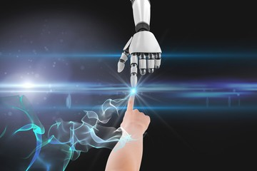 Human and robot touching their fingers against black background
