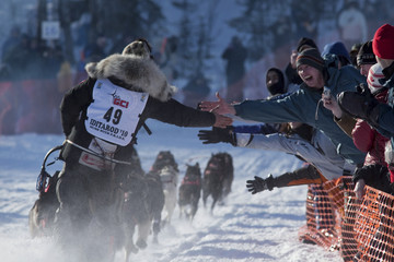 Mackey, reaches out to fans while charging down the trail just after the official start of the 2010 Iditarod Race in Willow