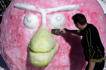 """A participant works on a snow sculpture for a competition during a snow festival called """"King Matjaz's Castles"""" in Crna na Koroskem"""