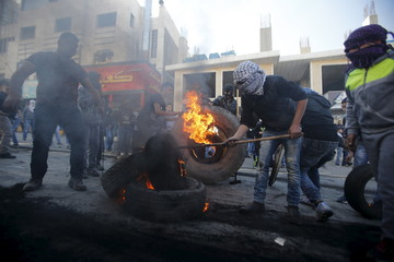 Palestinian protesters burn tyres during clashes with Israeli troops in the West Bank city of Hebron