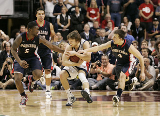 Saint Mary's Gaels' Matthey Dellavedova (C) is fouled by Gonzaga Bulldogs' Gary Bell Jr. (L) and Kevin Pangos in the closing seconds of overtime during the NCAA West Coast Conference Basketball Championship final in Las Vegas