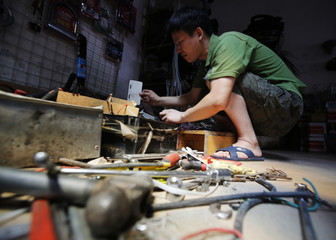 Chinese inventor Tao looks for usable parts at a bicycle shop in a second-hand market nearby his house in Beijing