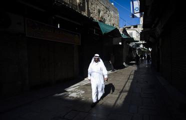A Muslim man walks past an Israeli flag in the Old City of Jerusalem