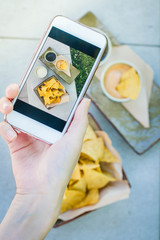 Hand's of men taking picture photo food with mobile smart phone. Top view. Mexican nachos with three kind sauce on photo