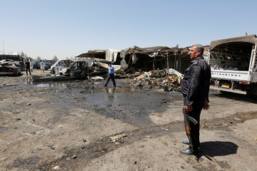 A member of the Iraqi security forces stands guard at the site of a car bomb attack in Rashidiya, a district north of Baghdad
