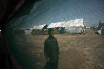 Internally displaced boy stands outside his family tent at the UNHCR Jalozai camp in Pakistan's northwest Khyber-Pakhtunkhwa province