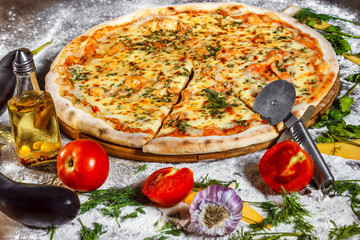 Tasty italian vegeterian pizza with fresh golden cheese and tomato at wooden background.