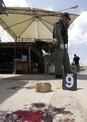 Thai security personnel inspect the site of a bomb blast at a tea shop in Songkhla province