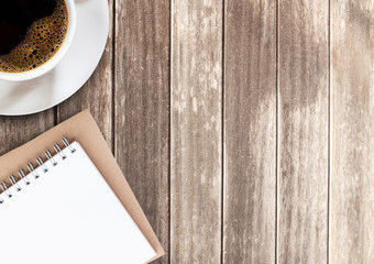 Top view cup of coffee and notebook on wooden table