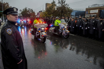 Police officers stand at attention as the honor guard arrives in the rain during the funeral service for slain New York City Police officer Randolph Holder in New York