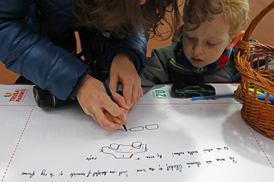 A mother helps child to draw wishes on world's longest letter addressed to Santa Claus during Guinness World Record attempt in Pantelimon