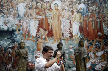 A tourist takes a photograph at the Buddhist Gangaramaya Temple in Colombo