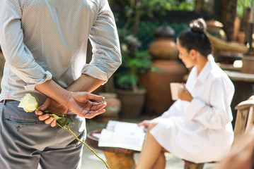 Man back and hand holding white rose with marriage ring making proposal of marriage, Blurred girl sitting and reading a magazine.