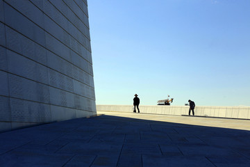 Tourists walk across the roof of the Opera House in Oslo