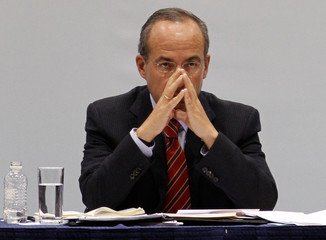 Mexico's President Felipe Calderon listens to a man demanding his attention during the launch of the federal government's latest strategy against violence and the lack of safety in the border city of Ciudad Juarez