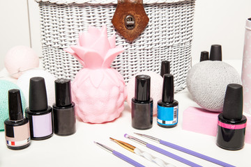 Accessories for nail decoration on a white table. Varnishes and nail brushes on the manicure table.