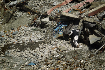 A man picks through the rubble of a collapsed hotel in Madyan at Pakistan's Swat Valley