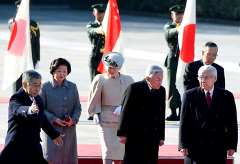 Singapore's President Tony Tan and his wife walk with Japan's Emperor Akihito and Empress Michiko on the red carpet during the welcoming ceremony at the Imperial Palace in Tokyo