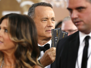 Actor Tom Hanks flashes his tickets as he arrives at the 71st annual Golden Globe Awards in Beverly Hills