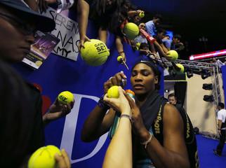 Singapore Slammers' Williams of the U.S. signs autographs after her match against Manila Mavericks' Flipkens of Belgium at the International Premier Tennis League in Singapore