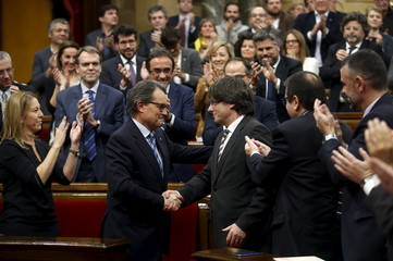 New Catalan President Carles Puigdemont is congratulated by outgoing Catalan President Artur Mas during the investiture session at the Catalunya Parliament in Barcelona