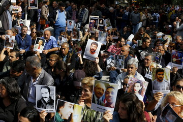Demonstrators hold portraits of those killed by Saturday's suicide bombings as they attend a commemoration in Ankara