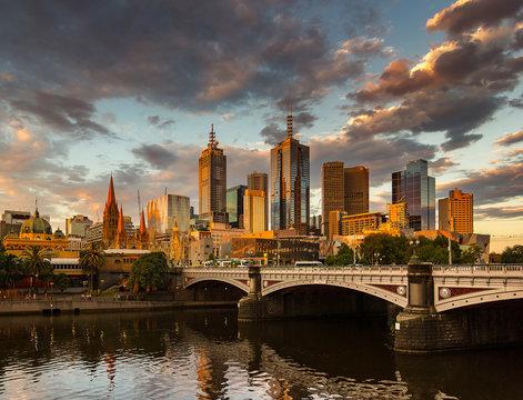 Melbourne City, Yarra River, Princes Bridge with Reflection Cityscape Skyline background under dramatic Golden Sky Sunset, Australia
