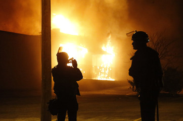 Police watch a burning building after a grand jury returned no indictment in the shooting of Michael Brown in Ferguson, Missouri