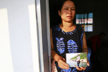 May Thein, mother of Win Zaw Htun, one of two Myanmar workers suspected of killing British tourist in Thailand, shows her son's picture at a monastery outside Yangon