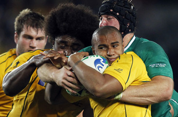 Ireland's Stephen Ferris tackles Australia Wallabies' Will Genia while Wallabies' Radike Samo supports during their Rugby World Cup Pool C match at Eden Park in Auckland